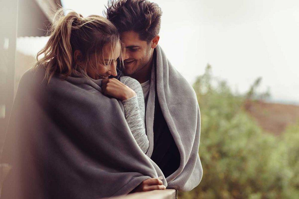 Coppia felice che condivide una coperta