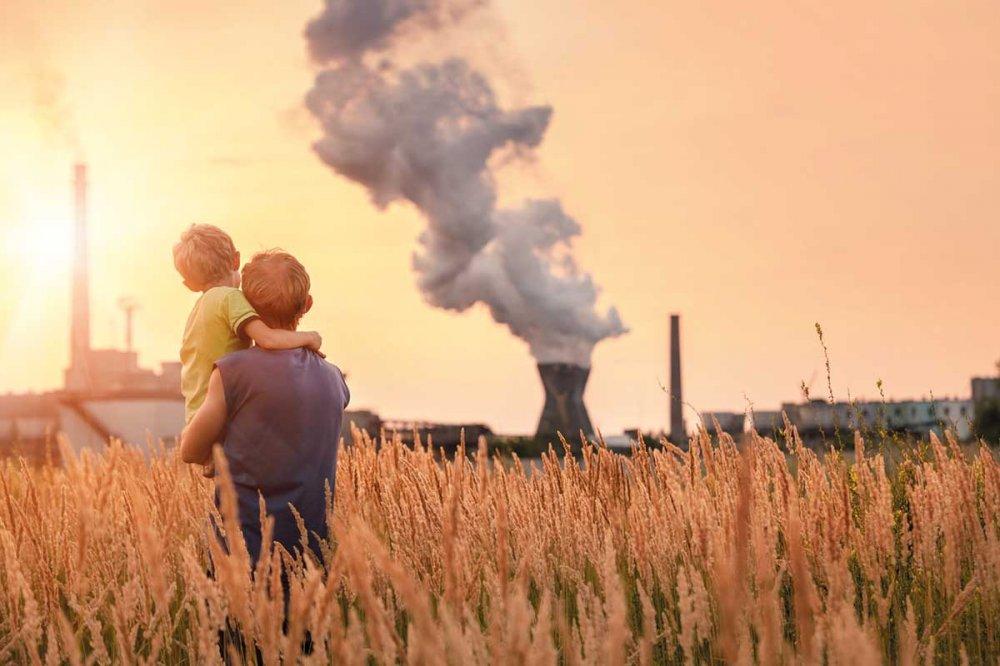 Due bambini in un campo di grano con ciminiere sullo sfondo