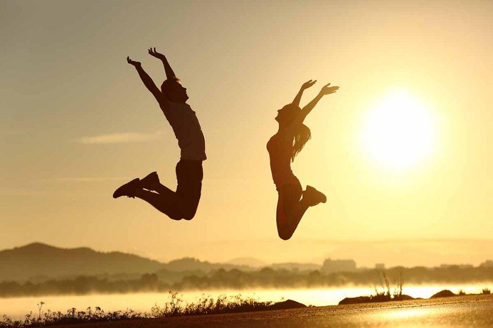 Coppia che salta in riva al mare al tramonto