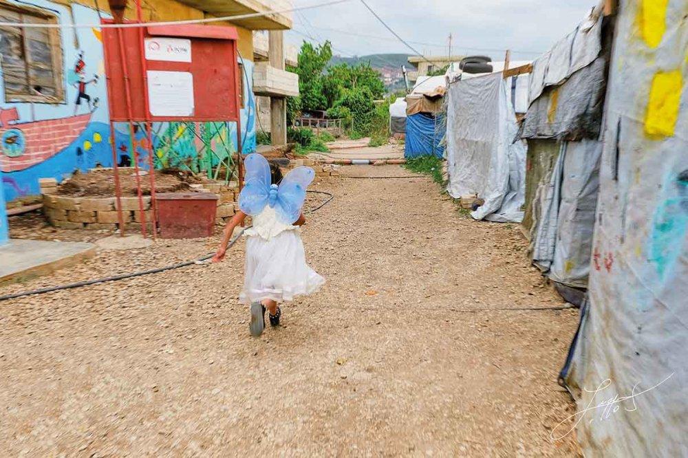 Bambina con ali di farfalla nel campo profughi di Akkar