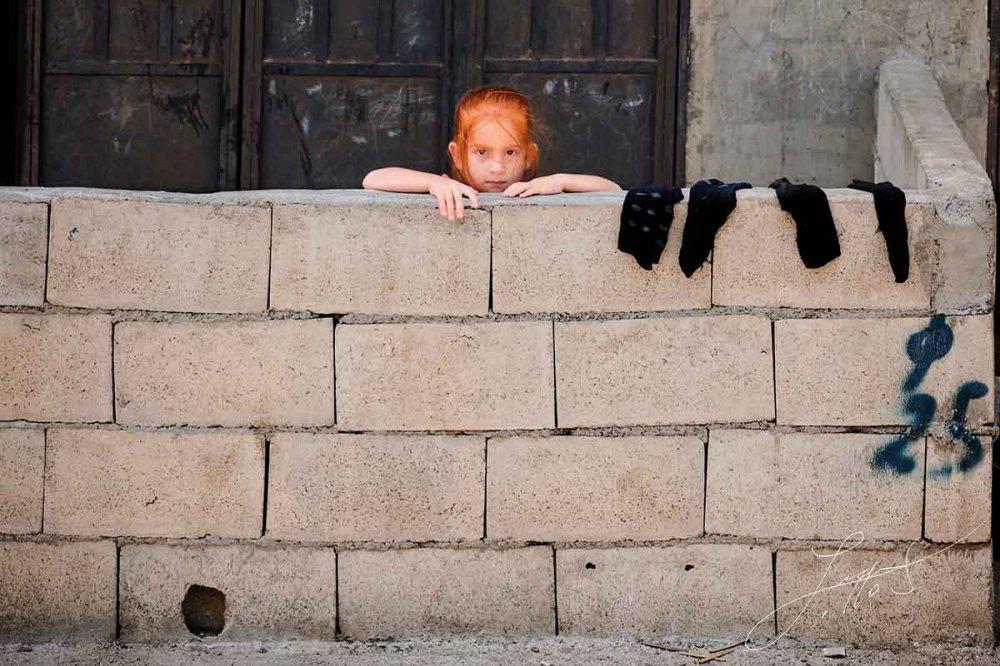 Bambina dietro al muretto ad Akkar