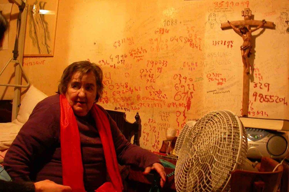 Alda Merini seduta sul suo letto con il muro coperto di appunti