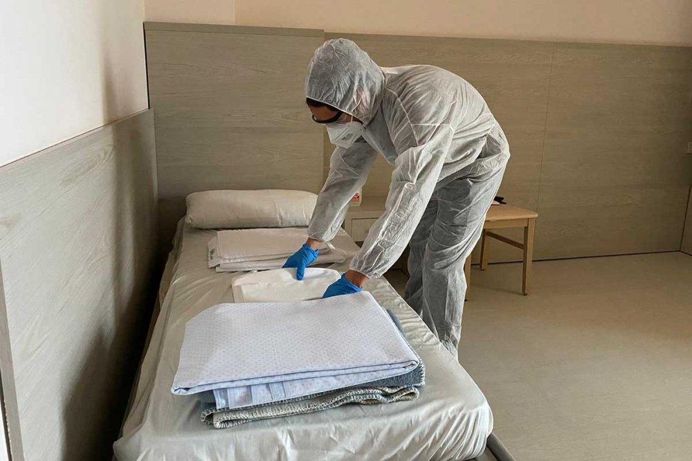 Un operatore con tuta, guanti e mascherina, prepara un letto