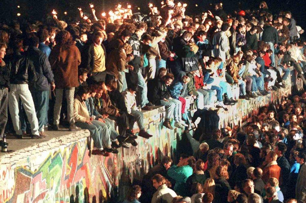 Giovani sul Muro di Berlino nella notte del 9 novembre 2019