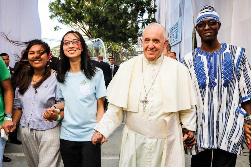 Papa Francesco cammina dando la mano a giovani di diverse nazionalità