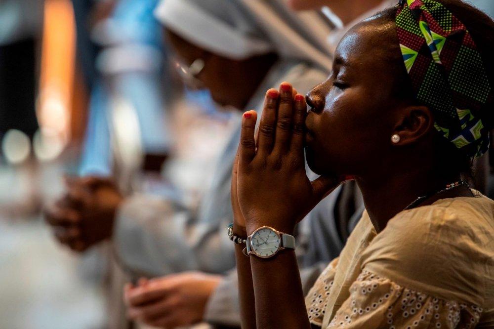 Donna nigeriana in preghiera a mani giunte