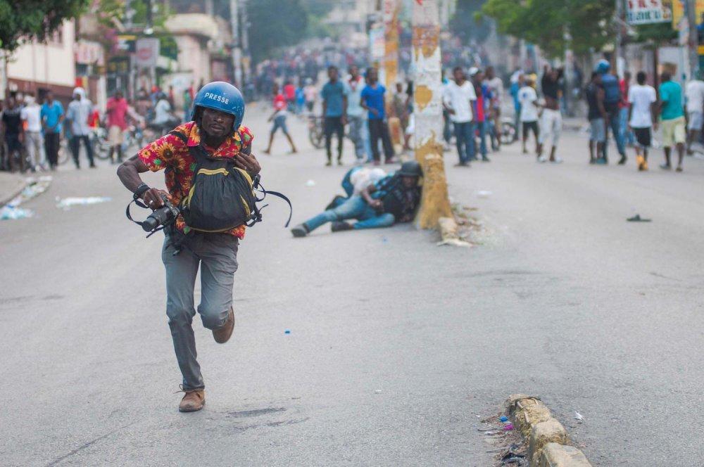 Un giornalista corre tra la gente che protesta contro il presidente Moise.