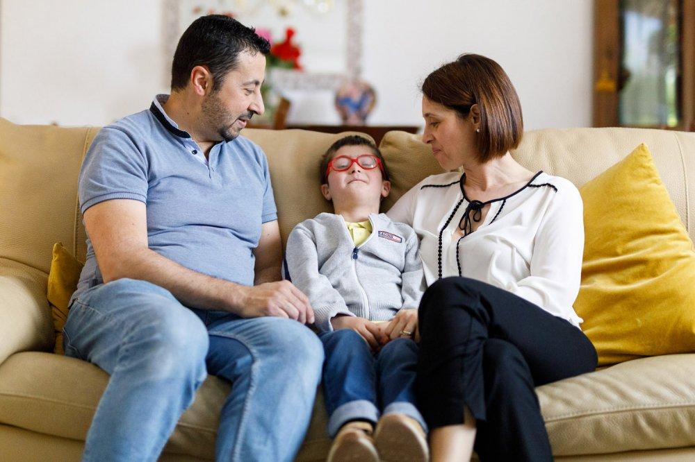 Genitori sorridenti sul divano con bambino