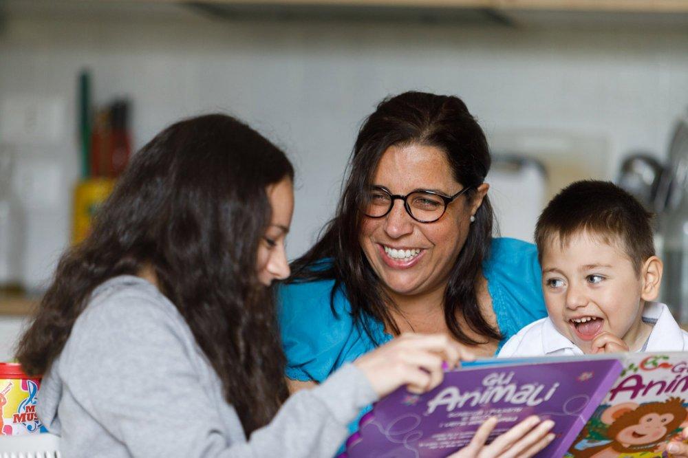 Mamma sorride leggendo libro ai bambini