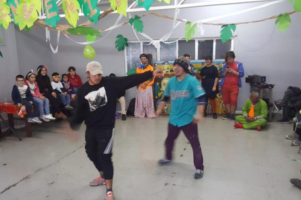 Ragazzi che ballano al centro della stanza con bambini intorno