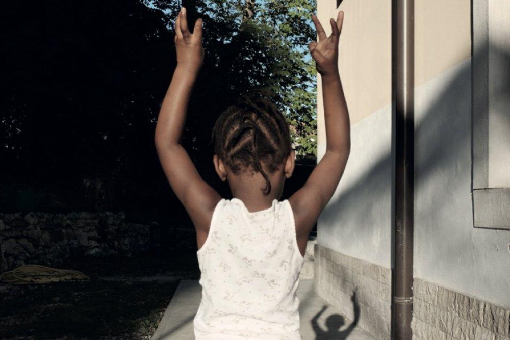 Bambina di colore di spalle con le mani in alto