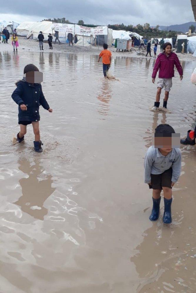 Bambini giocano nell'acqua che allaga il campo profughi