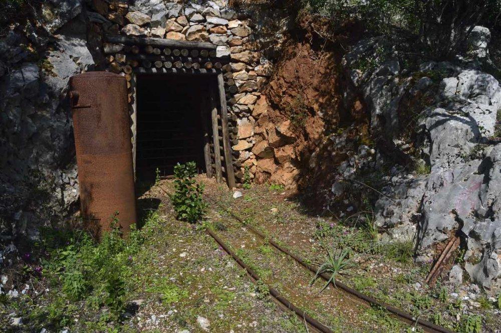 Entrata di una miniera abbandonata con rotaie arrugginite