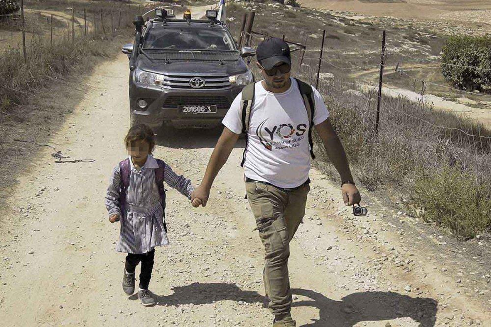 Volontario accompagna bambina a scuola