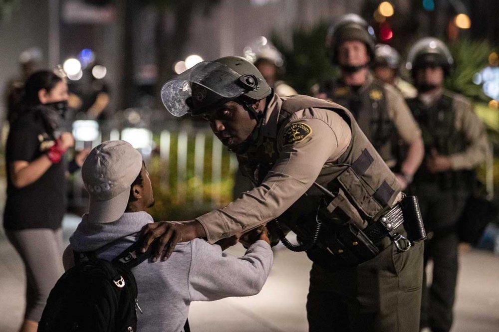 Un militare di colore stringe la mano ad un manifestante